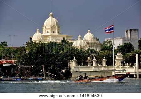 Samut Songkhram Thailand - December 17 2010: A longtail boat flying the Thai flag passes a domed mansion built on the banks of the Mae Klong River