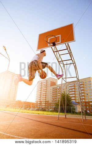 One guy play basketball at district sports ground against a backdrop of high-rise residential buildings. The player throws the ball into the ring in the jump and throws the ball at their feet.