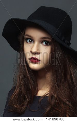 Girl with brown hair in a dark felt hat with red lips Close up