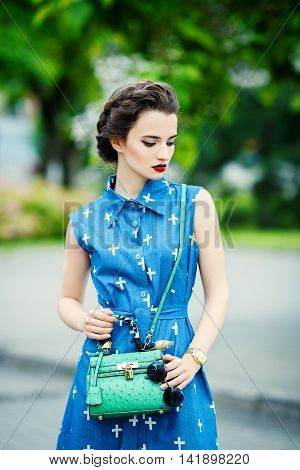 Young fashion woman with a green purse in hand on city background