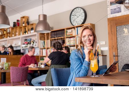 Young Woman In Cafe With Drink, Holding Tablet