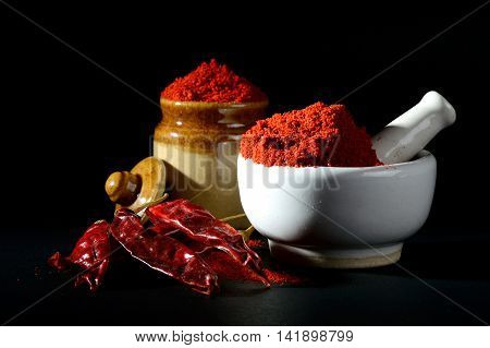 Red Chili Pepper powder in pestle with mortar and clay pot with Red Chili Peppers on black background