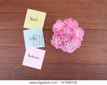 Handwriting word Work Life Balance on notepaper and pink Carnation flower with wood background (top view)
