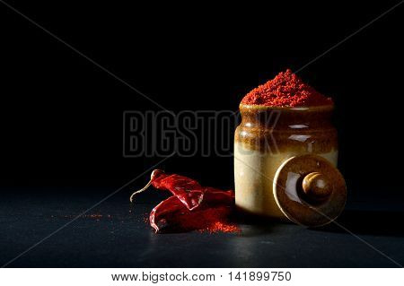 Red Chili Pepper powder in clay pot with Red Chili Peppers on black background