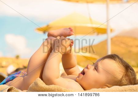 Happy baby on the beach playing with feet. Summer holidays concept.