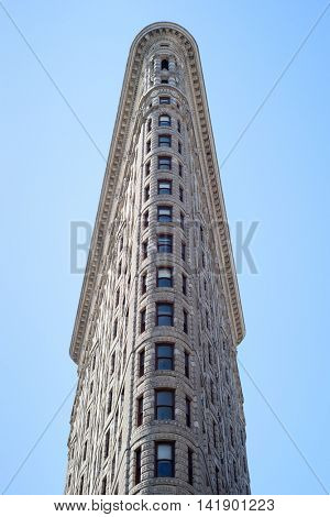 The Flatiron Building against a blue sky in New York City, USA on April 17, 2016. The Flatiron Building was originally known as the Fuller Building.
