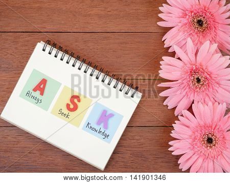 Word spell ASK and handwriting word Always Seek Knowledge and sweet pink Gerbera flower with wood background