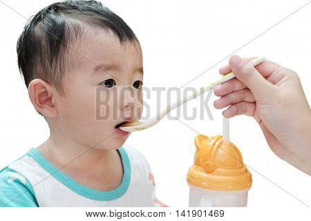 Closeup Of Asian Kid Boy Eating With Spoon On Highchair, Mother Is Feeding Baby.