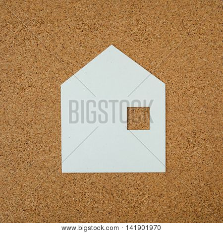 House paper shape by paper on cork background.