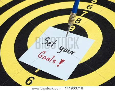 Handwriting Set your goal on notepaper with dart arrow and dart board. (Selective Focus)