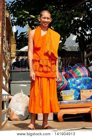 Chiang Mai Thailand - January 5 2013: Young Buddhist monk wearing an orange robe standing on the back of a pickup truck at Wat Suan Dok