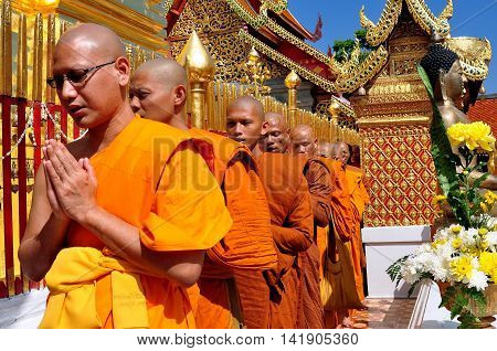 Chiang Mai Thailand - December26 2012: Monks their hands clasped in prayer walking in procession around the  golden Chedi at Wat Doi Suthep