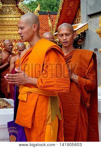 Chiang Mai, Thailand - December26, 2012:: Monks with their hands clasped in prayer walking in procession around the  golden Chedi at Wat Doi Suthep