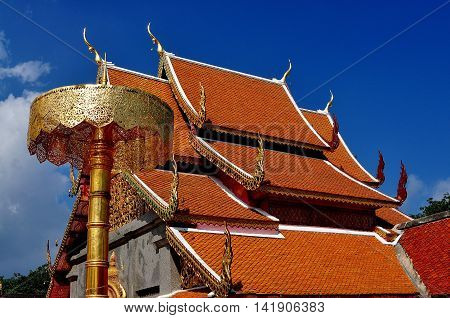 Chiang Mai Thailand - December 26 2012: Steeply pitched orange tiled roofs with dragon figures and chofah ornaments at Wat Doi Suthep