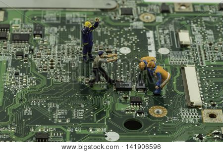 mini worker and technicial work on mainboard as a teamwork - can use to display or montage on products