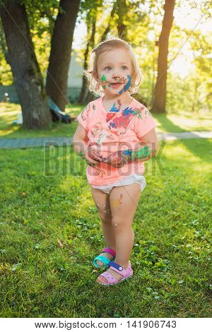 Two-year old girl stained in colors against green lawn