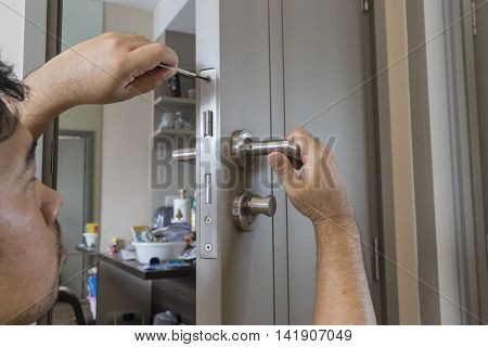 locksmith try to fix modern knob door by screwdriver - can use to display or montage on products