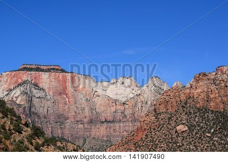 Majestic Mountain and Plateau of red, white, and grey, a deep-blue sky, and green shrubbery, late morning, Zion National Park