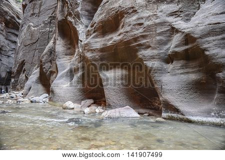Interesting Rock Formations and Carvings on a Canyon Wall, with a clear rushing river, in The Narrows, Zion National Park