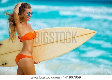 Girl of the European appearance with a beautiful figure in mirror sun glasses blue,brunette with long hair in bikini orange,posing against the backdrop of the blue ocean with the white foam of the waves, keeps on hand a surfboard