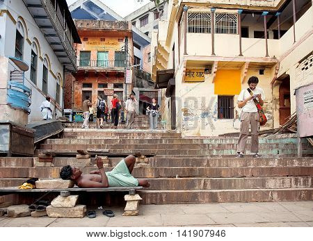 Varanasi, India - Jule 30, 2011: Peoples on the ghats, embankments made in steps of stone slabs along the Ganges river bank where pilgrims perform ritual ablutions.