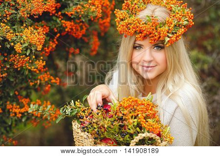 Young beautiful woman with long blonde straight hair,light makeup,wearing a beige jacket,on the head wears a wreath of orange of Rowan berries,spending time outdoors in the Park in the middle of autumn,posing near bushes ripe Rowan