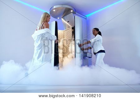 Full length woman entering freezing booth at the cosmetology clinic. Female taking cryotherapy treatment with beautician standing at the capsule door.
