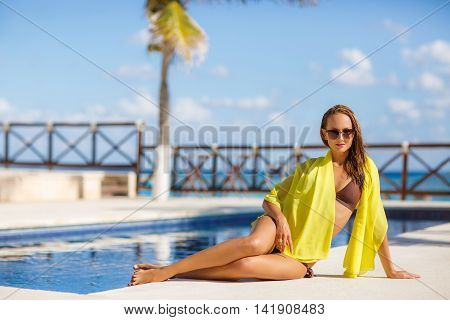 A slender young woman with a nice figure,brunette with long flowing hair,wearing earrings ears,wearing dark sun glasses and bikini in brown on the shoulders draped a yellow pareo,spends time near the pool with blue water in the summer