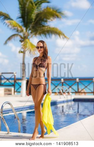 A slender young woman with a nice figure,brunette with long flowing hair,wearing earrings ears,wearing dark sun glasses and bikini in brown,hand holds yellow pareo,spends time near the pool with blue water in the summer