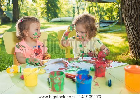 Two-year old girls painting with poster paintings and sitting at a table together against green lawn
