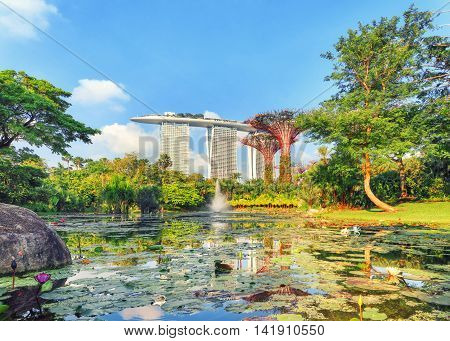 Singapore, Republic of Singapore - May 5, 2016: Gardens by the Bay with Supertree grove and Marina bay Sands hotel reflecting in lake at sunrise