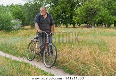 Senior peasant standing on a country road with old rusty bicycle and dream about Grand Tour would ride through his village