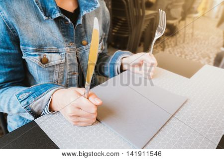 Hungry woman holding knife and fork waiting for food food or restaurant concept warm light tone