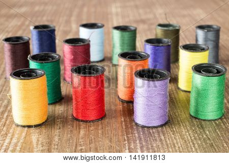 Bobbins with colorful threads on old wooden table background