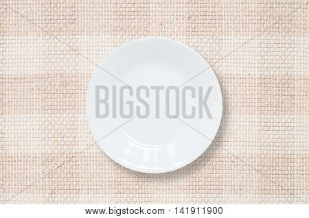 Closeup white ceramic dish on brown fabric mat textured background at the center on dining table in top view with copy space