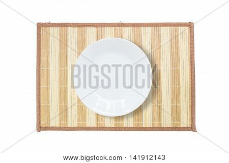 Closeup white ceramic dish on wood mat textured background on dining table isolated on white background in top view