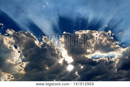Sinking sun sends out rays from behind a cloud