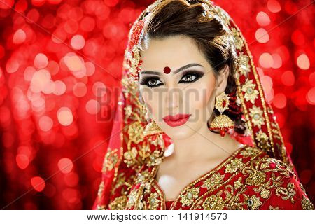 Portrait of a beautiful female model in traditional ethnic Indian Pakistani bride costume with heavy jewellery and makeup