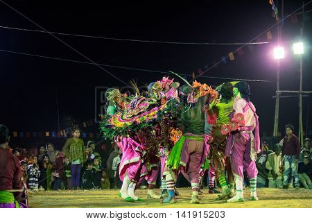 BAMNIA PURULIA WEST BENGAL INDIA - DECEMBER 23RD 2015 : Dancer dressed as monsters carrying out their dead leader Chhau Dance festival. It is a very popular Indian tribal martial dance performed at night amongst spectators.
