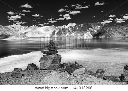 Rocks and reflection of Mountains on Pangong tso (Lake) with blue sky. It is huge lake in Ladakh extends from India to Tibet. Leh Ladakh Jammu and Kashmir India. Black and white stock image.