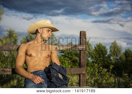 Portrait of sexy shirtless muscular farmer or cowboy in hat looking at camera while leaning on wooden fence in countryside