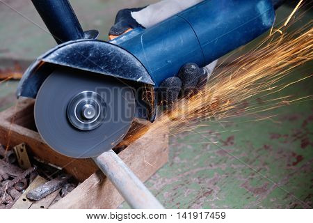 Worker  grinds steel tube with a grinding machine