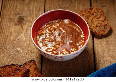 Goulash soup and sliced bread on a wooden table
