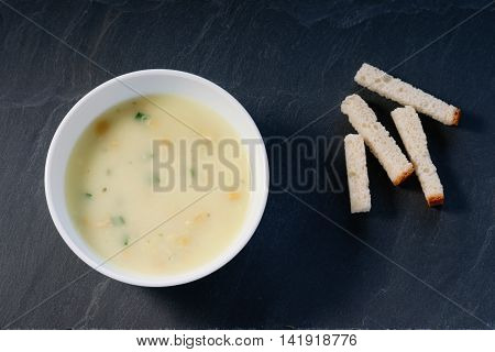 Cream soup and bread croutons on a black stone plate
