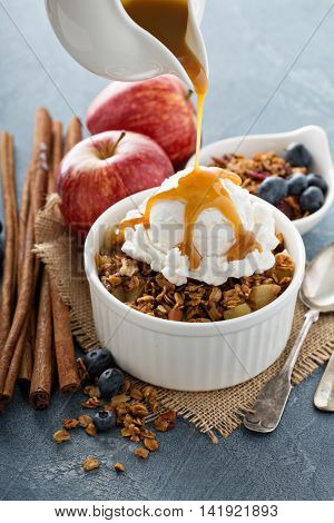 Apple crisp with vanilla ice cream with caramel sauce pouring over - homemade fall dessert