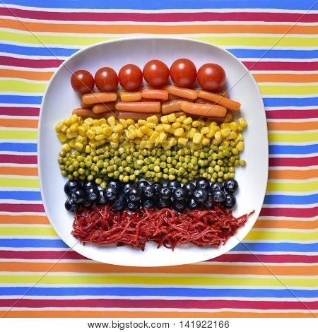 high-angle shot of a plate with some different vegetables forming the rainbow flag, as tomatoes, baby carrots, sweet corn, peas, blueberries and beetroot, on a colorful strip-patterned background