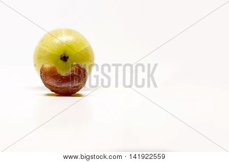 A piece of Indian gooseberry candy with a gooseberry in the blurred background