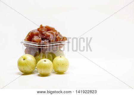 A bunch of gooseberry candies in a bowl with some gooseberries in the blurred foreground