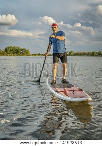 senior male on stand up paddleboard on a lake in northern Colorado