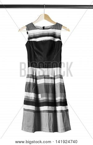 Black and white dress on wooden clothes rack isolated over white